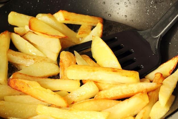 Batatas jovens fritas em óleo fervente para uma frigideira