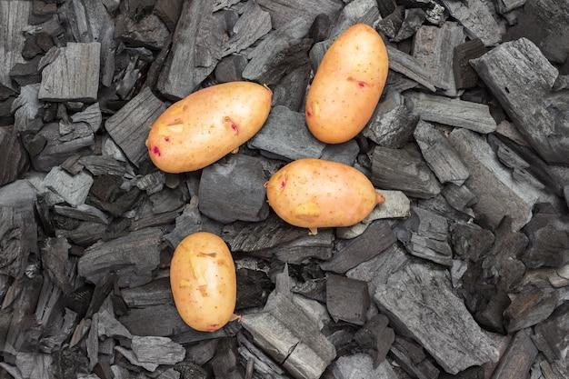 Batatas jovens inteiras no carvão. alimentos grelhados. nutrição saudável orgânica.