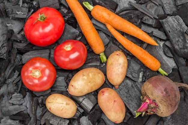Batatas jovens inteiras, tomates, cenouras, beterraba no carvão. alimentos grelhados. nutrição saudável orgânica.