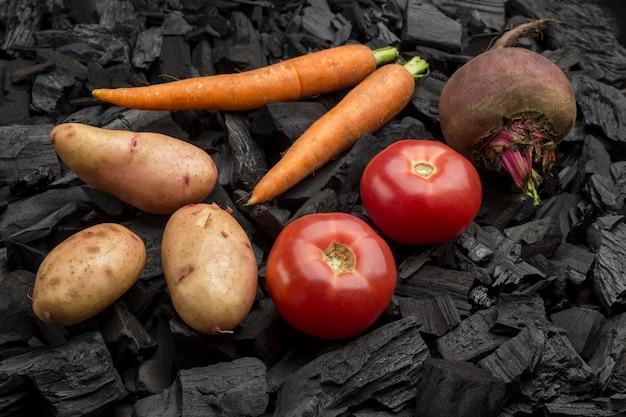 Batatas jovens inteiras, tomates, cenouras, beterraba no carvão.