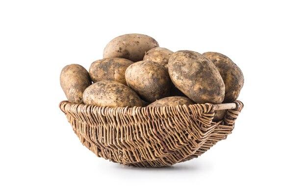 Batatas maduras e sujas em uma cesta de madeira, isolada no fundo branco.