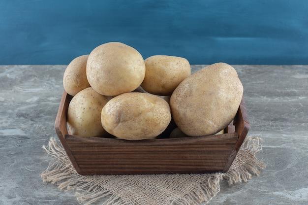 Batatas na caixa, na toalha, na mesa de mármore.