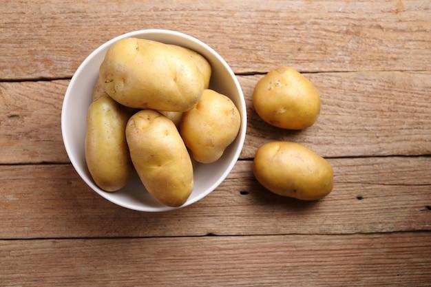 Batatas na tigela em fundo de madeira
