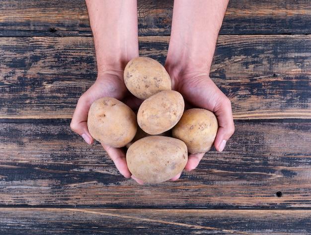 Batatas nas mãos de um homem em uma mesa de madeira escura