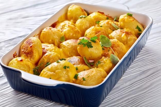 Batatas novas com queijo cheddar assadas no forno e molho de manteiga de queijo cheddar em uma assadeira sobre uma mesa de madeira branca
