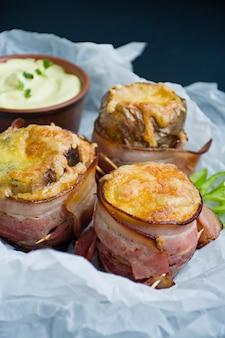 Batatas novas cozidas envolvidas no bacon, no queijo superior, no microgreen, no molho e em legumes frescos.