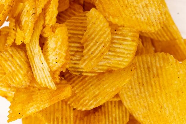 Batatas onduladas douradas. pilha de fichas em um fundo branco. não é uma dieta saudável. fast food frito