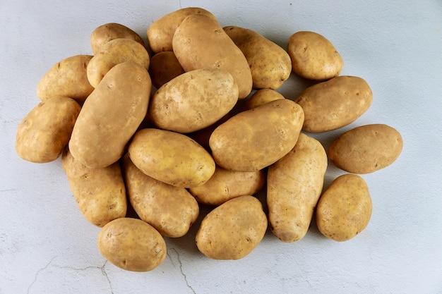 Batatas orgânicas cruas na superfície branca