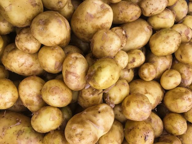Batatas orgânicas frescas em carrinho no fundo do supermercado