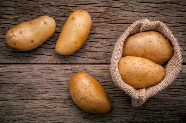 Batatas orgânicas frescas no saco da causa do cânhamo no fundo de madeira.