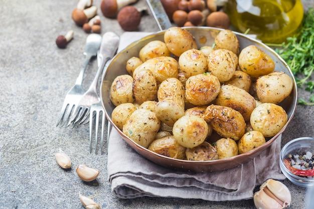 Batatas pequenas assadas com verduras e óleo de alho em uma panela sobre uma pedra cinza