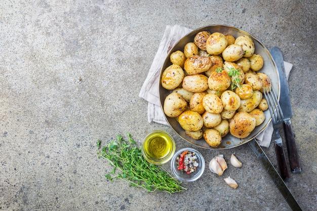 Batatas pequenas assadas com verduras e óleo de alho sobre pedra cinza