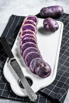 Batatas roxas cortadas cruas em uma placa de desbastamento branca. fundo cinza. vista do topo