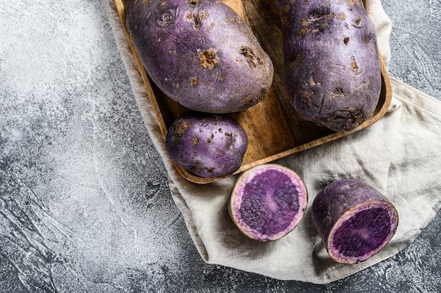 Batatas roxas cruas em uma tábua.