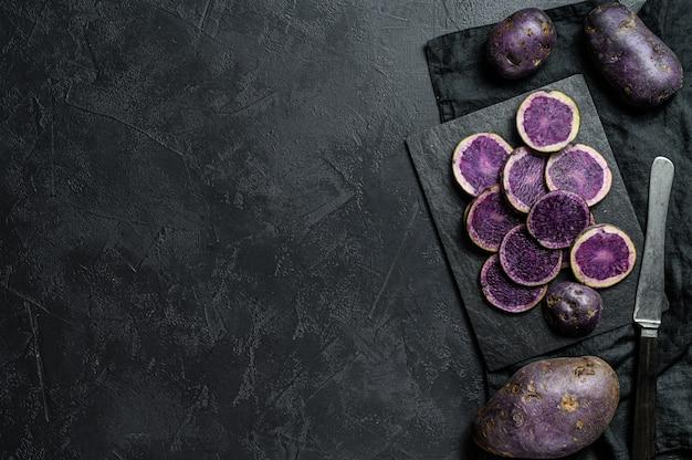 Batatas roxas em fatias cruas. fundo preto. vista do topo. espaço para texto