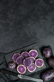 Batatas roxas em fatias cruas.