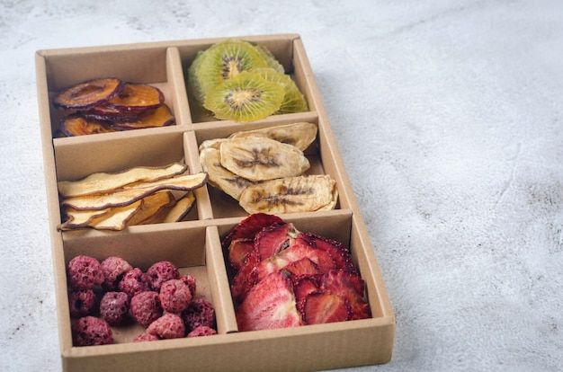Batatas secas artesanais sortidas em caixa em fundo cinza. conceito de alimentação saudável, lanche, sem açúcar. preparando pacote de cuidados, caixa de presente sazonal. cesta ecológica para ação de graças, natal,