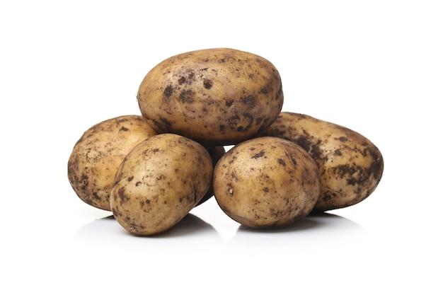 Batatas sujas em uma superfície branca
