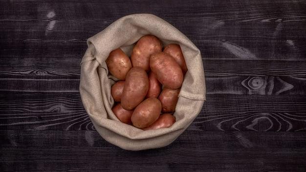 Batatas vermelhas cruas em um saco sobre um fundo de mesa de madeira rústica preta, preparada para limpar e fatiar enquanto cozinha um prato frito, guisado ou fervido.