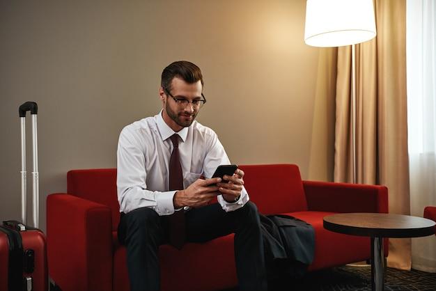 Bate-papo de negócios. homem de negócios de óculos com mala e tablet sentado no sofá na entrada do hotel