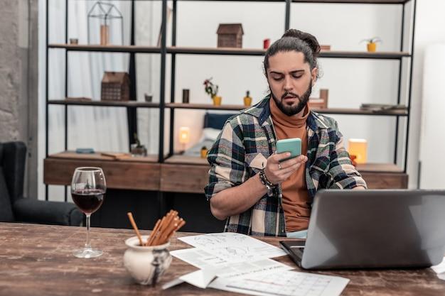 Bate-papo móvel. homem sério e simpático sentado em frente ao laptop enquanto digita uma mensagem em seu smartphone