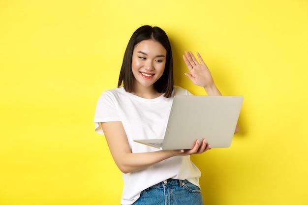 Bate-papo por vídeo feliz mulher asiática no laptop, dispensando a mão na câmera do computador e dizendo olá, em pé sobre fundo amarelo.
