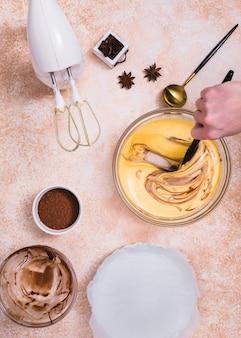 Batedeira elétrica; cacau em pó; anis e uma pessoa misturando a massa de bolo com espátula