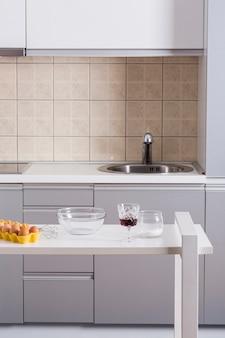 Batedor de ovos; tigela; taças de vinho e farinha na mesa na cozinha