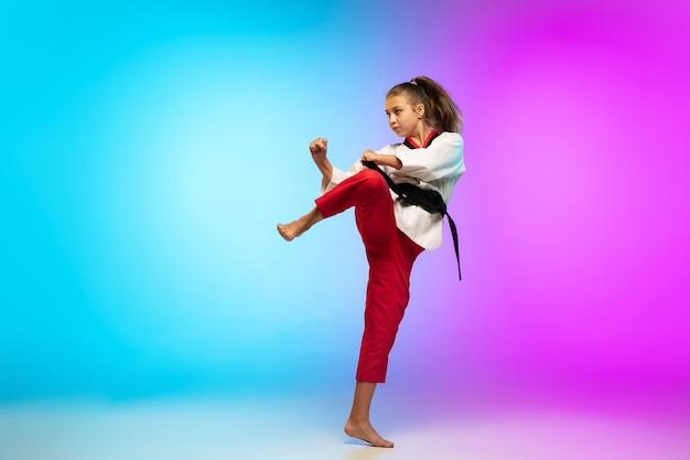 Batendo. karatê, garota de taekwondo com faixa preta isolada em fundo gradiente em luz de néon. pequeno modelo caucasiano, garoto do esporte, treinamento em movimento e ação. esporte, movimento, conceito de infância.
