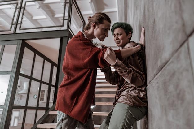 Bater na namorada. homem bravo e agressivo batendo em sua jovem namorada de cabelo verde