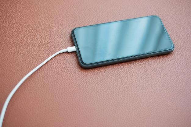 Bateria de carregamento do telefone móvel esperto no sofá de couro em casa. tecnologia, compartilhamento múltiplo e conceitos de estilo de vida