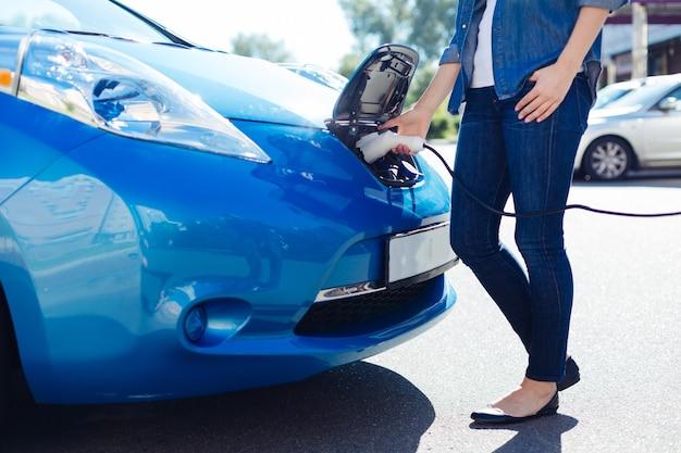 Bateria fraca. mulher agradável e habilidosa segurando um carregador elétrico e ligando-o ao carro enquanto está na estação de carregamento