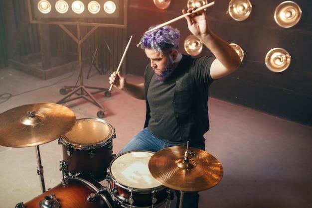 Baterista barbudo com cabelos coloridos no palco