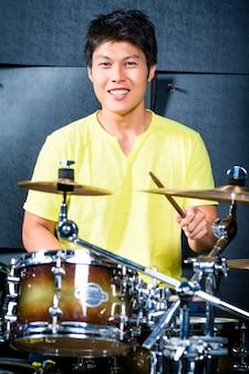 Baterista de músico asiático no estúdio de gravação