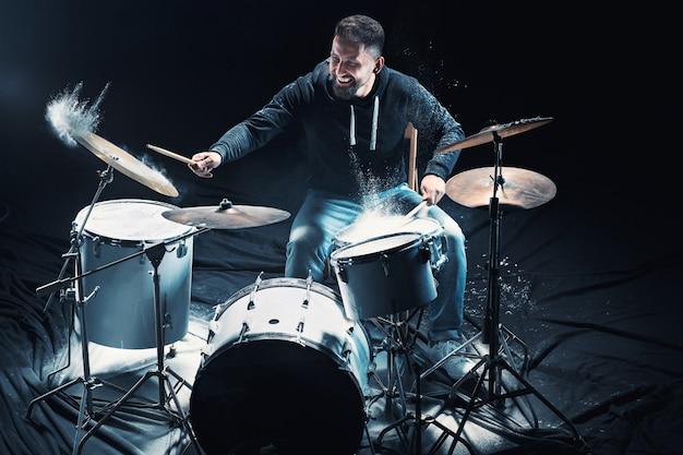 Baterista ensaiando bateria antes de show de rock homem gravando música na bateria