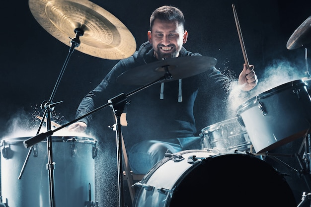 Baterista ensaiando bateria antes do show de rock. homem gravando música na bateria em estúdio com efeito show na forma de farinha