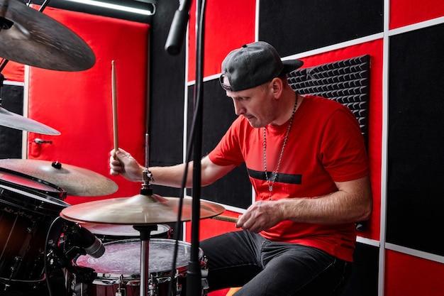 Baterista profissional moderno toca bateria em uma base de ensaio, estúdio de gravação vermelho e preto