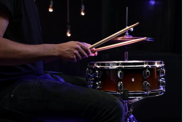 Baterista tocando baquetas em uma caixa no escuro. conceito de concerto e performance ao vivo.