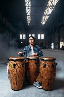 Baterista tocando bateria de bongô de madeira, música batida