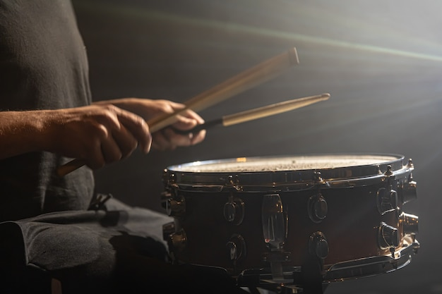 Baterista tocando percussão, caixa de bateria no palco sob os holofotes, cópia espaço.