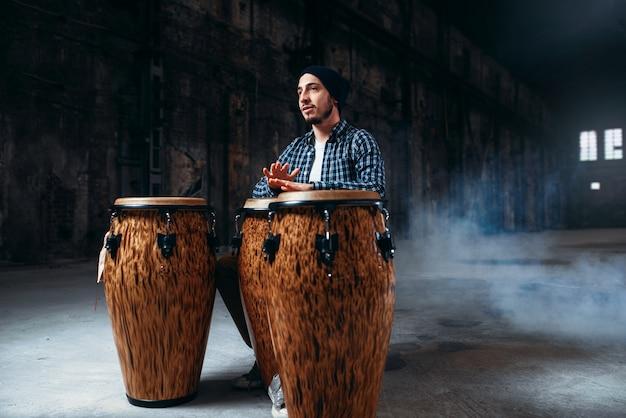 Baterista tocando tambores de madeira na loja da fábrica