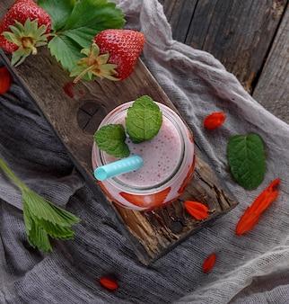 Batido caseiro de iogurte e morangos frescos em uma jarra de vidro, vista superior