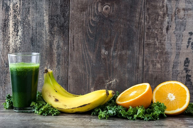 Batido com couve, banana e laranja em fundo de madeira