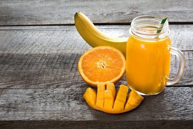 Batido com frutas tropicais: manga, banana, laranja em um frasco de pedreiro de vidro no fundo de madeira.