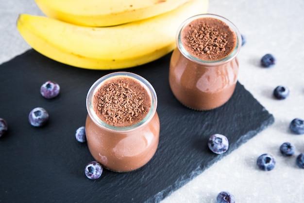 Batido da banana do chocolate com sementes e mirtilo do chia em um fundo da ardósia e da pedra.