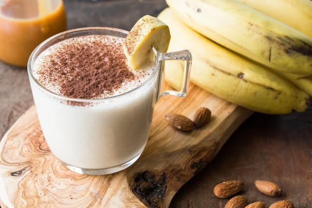 Batido de banana de chocolate fresco feito sobre uma mesa de madeira. foco seletivo. milk-shake com nozes. dieta proteica. concep saudável de alimentos e bebidas
