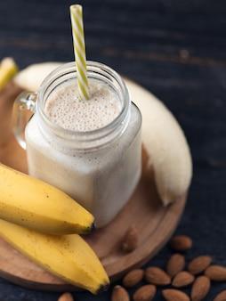 Batido de banana fresca em uma mesa de madeira em uma jarra