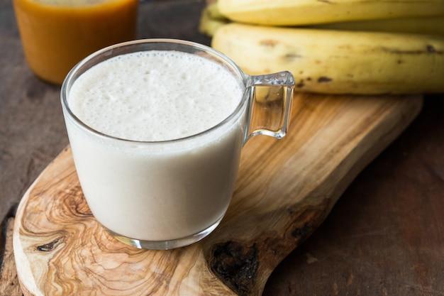 Batido de banana fresco feito de caramelo em uma mesa de madeira. foco seletivo. milk-shake com nozes. dieta proteica. concep saudável de alimentos e bebidas