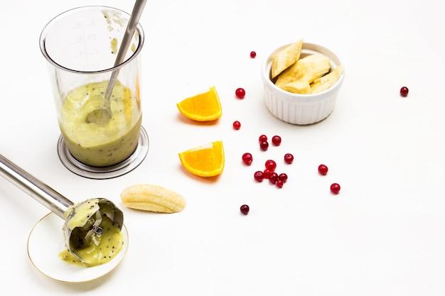 Batido de banana no copo do liquidificador. picador de metal no pires. banana picada e duas fatias de laranja. kiwi na mesa. vista do topo