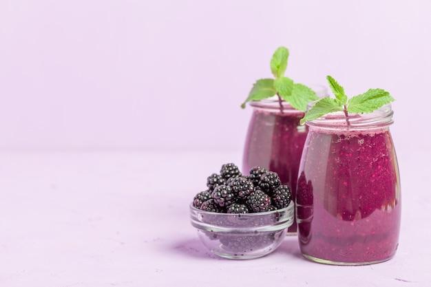 Batido de blackberry - bebida orgânica crua com as bagas maduras frescas da floresta no fundo violeta pastel.